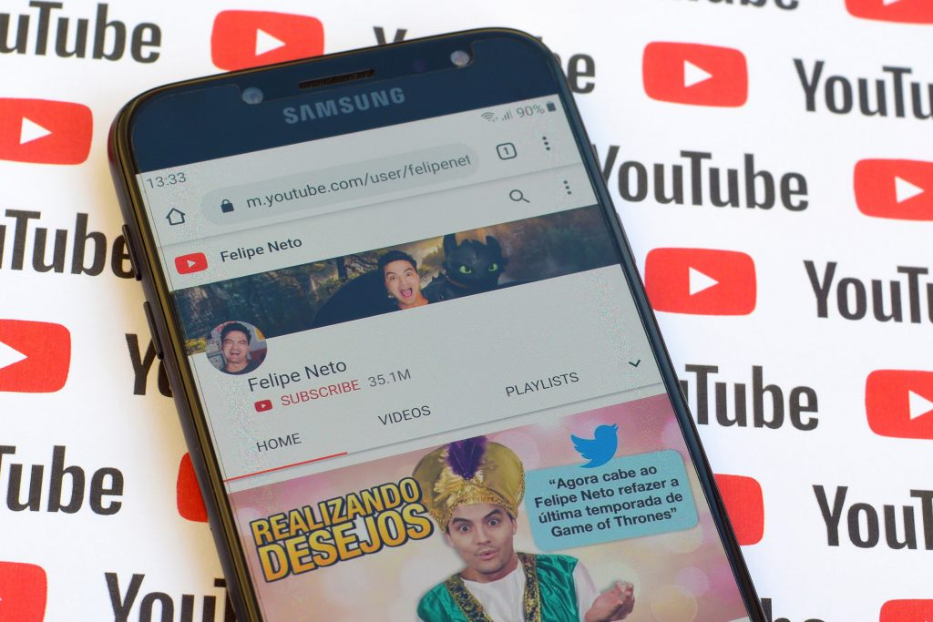 Felipe Neto official youtube channel on smartphone screen on paper youtube background